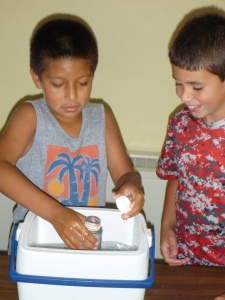 Students practice taking a water sample.